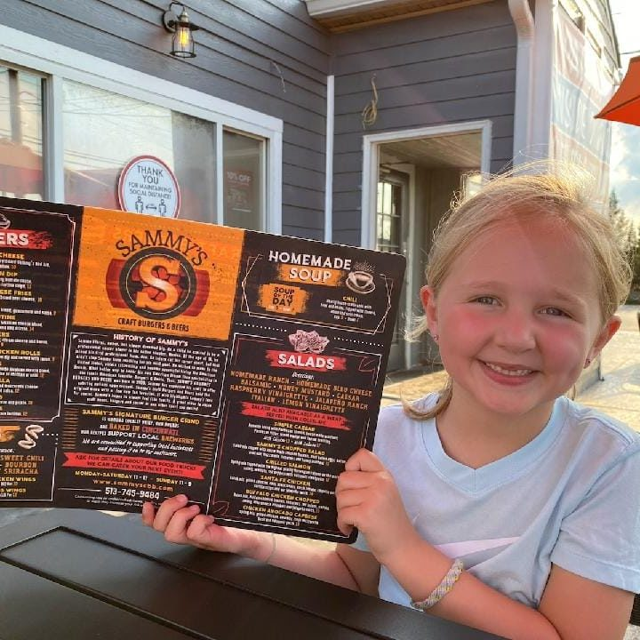 Happy girl holding Sammy's menu